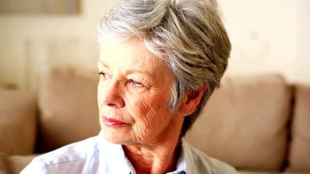 vídeos de stock e filmes b-roll de infeliz mulher idosa sentada no sofá - old lady