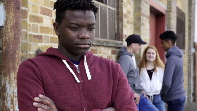 vídeos de stock e filmes b-roll de unhappy teenage boy being gossiped about by peers - ameaça