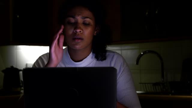 donna infelice a casa con il computer vittima di bullismo online sui social media - violenza donne video stock e b–roll