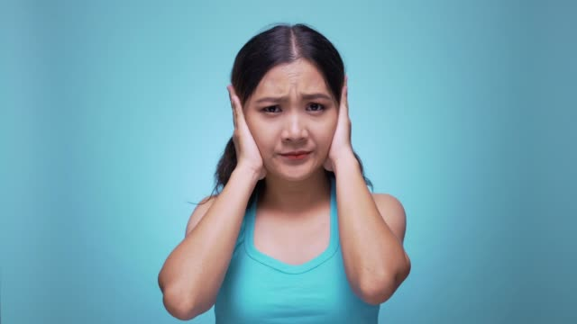 Unhappy woman closing ears on isolated blue background 4k
