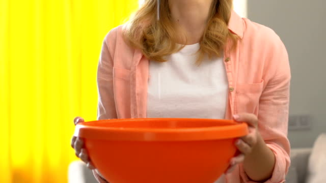 unhappy woman holding bowl and looking water pouring from ceiling, trouble - soffitto video stock e b–roll