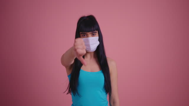 Unhappy young brunette woman in medical mask showing thumbs down gesture isolated on pink background