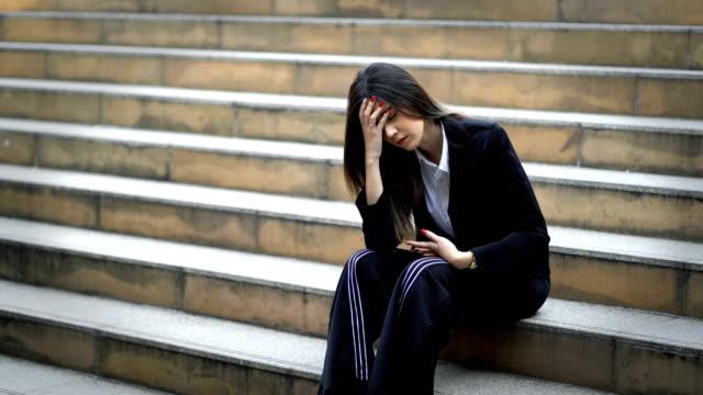4k不幸な若いビジネスウーマンは、現代の都市の背景で階段に座ってイライラし、ストレスウーマンは頭痛と頭に触れています - 女性 落ち込む点の映像素材/bロール