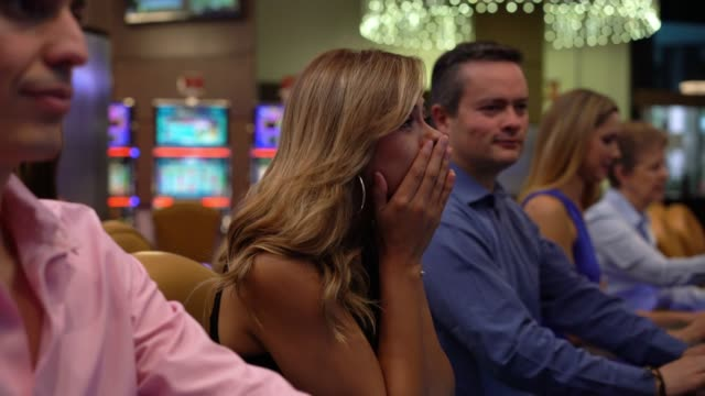 Unhappy young woman loosing money at the casino on a slot machine
