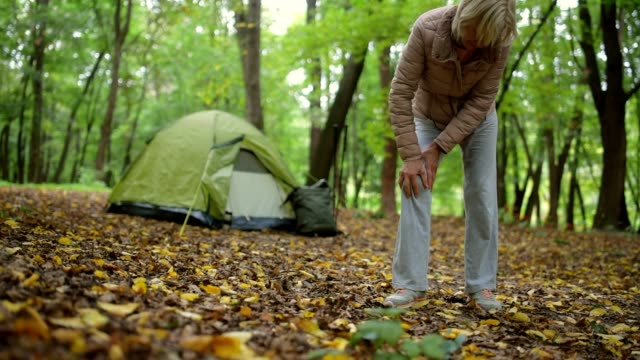 Unhealthy elderly woman having a pain in the knee Need medical help. Full length of a pleasant elderly woman standing in the forest while suffering from a pain in the knee knee stock videos & royalty-free footage