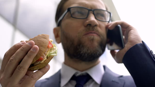 vídeos de stock e filmes b-roll de unhealthy nutrition, busy businessman talking on phone and eating burger lunch - sanduíche