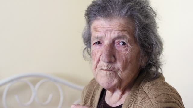 Unhealthy old woman eating, looking camera at home video