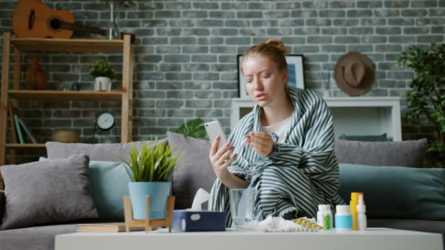 vídeos de stock e filmes b-roll de unhealthy teenager using smartphone for video consultation with doctor talking - doença