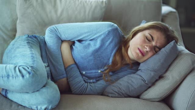 vídeos de stock e filmes b-roll de unhealthy young woman with stomachache - dor