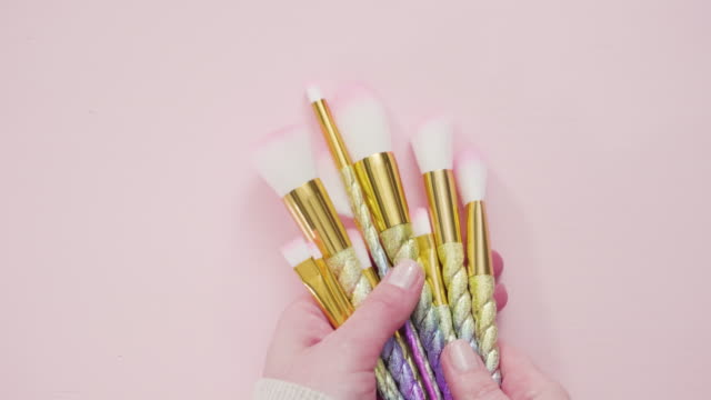 unicorn color makeup brushes on a pink background. - kompozycja flat lay filmów i materiałów b-roll