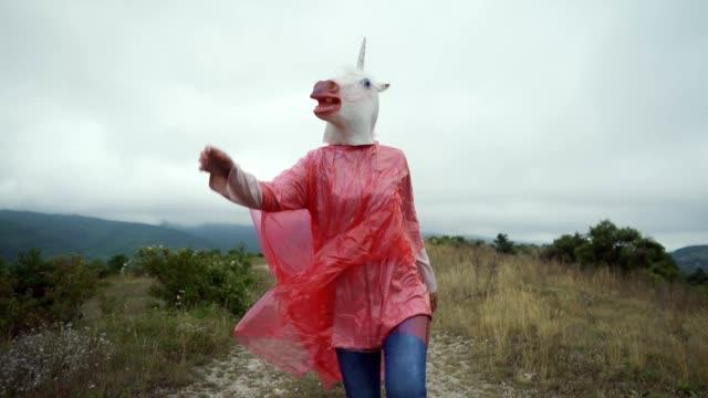 vídeos y material grabado en eventos de stock de unicornio saltando en un impermeable - unicornio