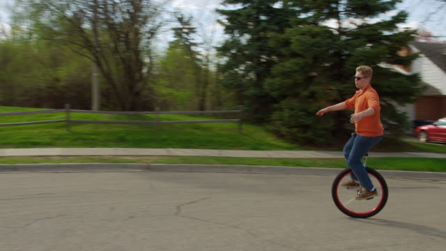 Unicyclist starts up and rides around suburban street video