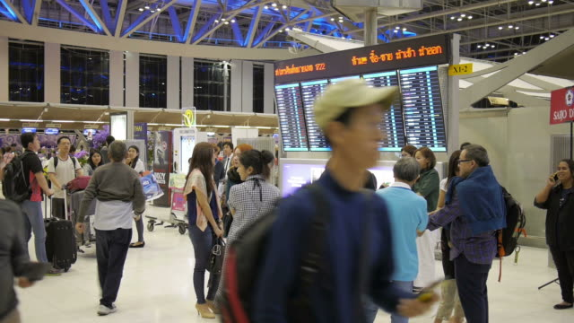 Unidentified air passengers walk by and stop at a departures timetable in the Suvarnabhumi International Airport video