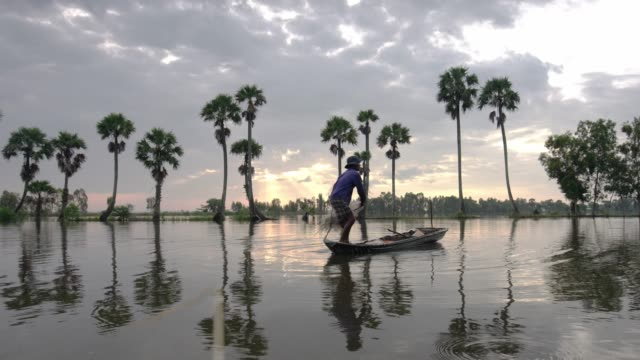 Unidentified fishers throw fish net to catch fish a lake in the morning