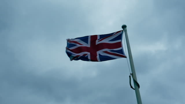 Union Jack flag blowing in strong winds against an overcast sky, filmed in 5 X slow motion. video