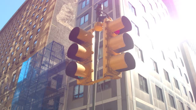 CLOSE UP: Unique New York City yellow hanging traffic lights on sunny summer day video