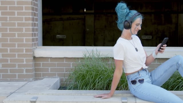 Unique, Spunky, Fashionable Young Millennial Woman Listening to Wireless Bluetooth Headphones and Scrolling Social Media or Playlist Music or Podcasts Outdoors in the Summer