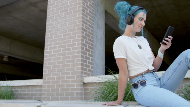 Unique, Spunky, Fashionable Young Millennial Woman Listening to Wireless Bluetooth Headphones and Scrolling Social Media or Playlist Music or Podcasts Outdoors in the Summer Unique, Spunky, Fashionable Young Millennial Woman Listening to Wireless Bluetooth Headphones and Scrolling Social Media or Playlist Music or Podcasts Outdoors in the Summer bluetooth stock videos & royalty-free footage