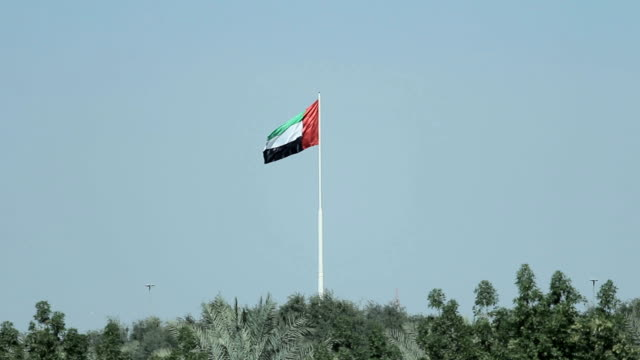 A United Arab Emirates flag flying against clean and tranquil sky. UAE celebrates it's national day on 2nd December every year A United Arab Emirates flag flying against clean and tranquil sky in Ajman. UAE celebrates it's national day on 2nd December every year. national landmark stock videos & royalty-free footage