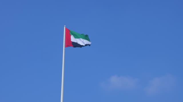 birleşik arap emirlikleri bayrağı mavi gökyüzü arka plan abu dabi kent üzerinde uçan - uae flag stok videoları ve detay görüntü çekimi