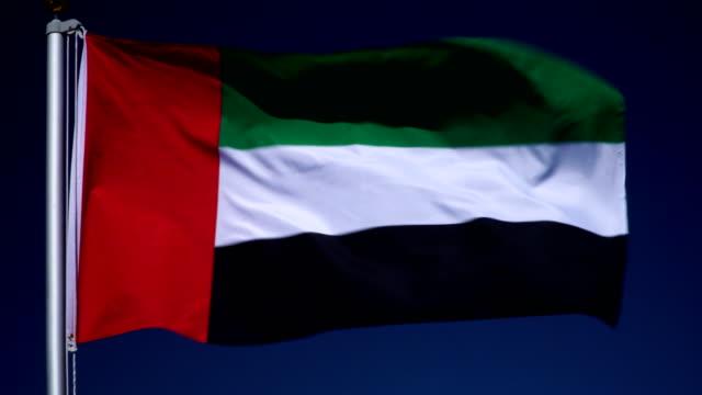4k: birleşik arap emirlikleri bayrağı bayrak direği önünde mavi gökyüzü açık havada (bae) - uae flag stok videoları ve detay görüntü çekimi