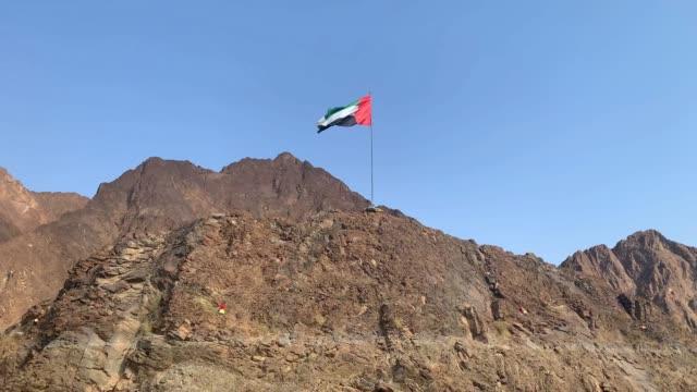 flaga zjednoczonych emiratów arabskich macha na szczycie wzgórza w środku jeziora hatta na tle błękitnego nieba. - uae flag filmów i materiałów b-roll