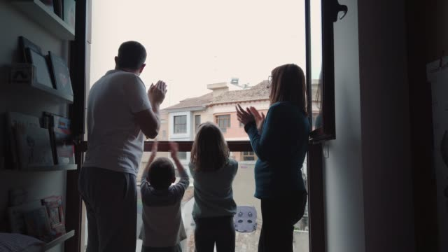 United family clapping in the window Family applauds medical staff from their balcony in support of health workers during the Coronavirus pandemic thank you stock videos & royalty-free footage