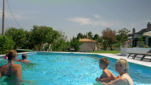 vídeos de stock e filmes b-roll de reino família em casa jogando bola piscina insuflável - brinquedos na piscina