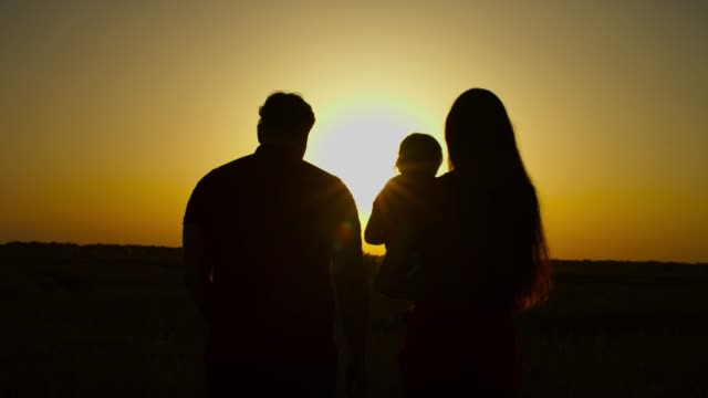 United family with baby girl walking at sundown