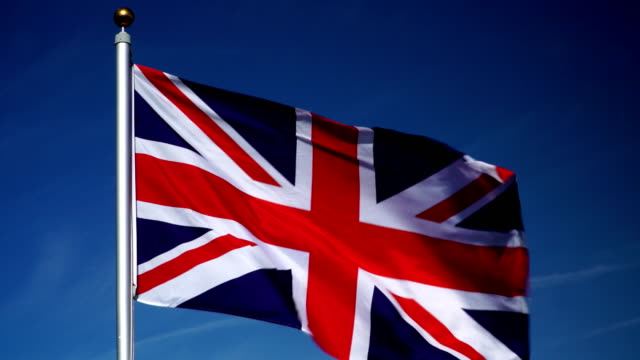 4K: United Kingdom Flag on Flagpole in front of Blue Sky outdoors (UK) video