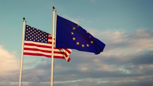 vidéos et rushes de les drapeaux des états-unis et de l'union européenne sur un mât montrent des relations politiques. - europe