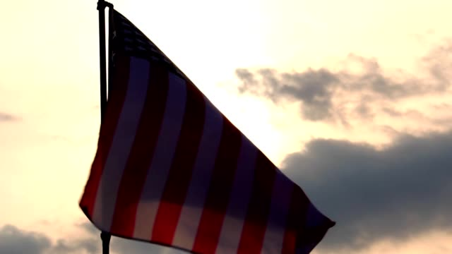 united states flag with a blue sky, and the light of sunset - fourth of july стоковые видео и кадры b-roll