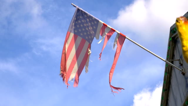 United States frayed flag waving in the wind in 4K Professional video of United States frayed flag waving in the wind in 4K slow motion 60fps torn stock videos & royalty-free footage