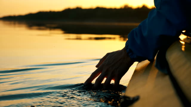 vídeos de stock e filmes b-roll de unity with nature, man puts his hand into the water while sitting in kayak against golden sunset, camera slow motion - dedo humano