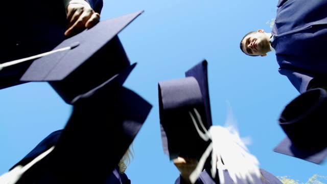 Diplômés de l'Université de lancer leur tradition d'étudiant bouchons carrés, vue de dessous - Vidéo