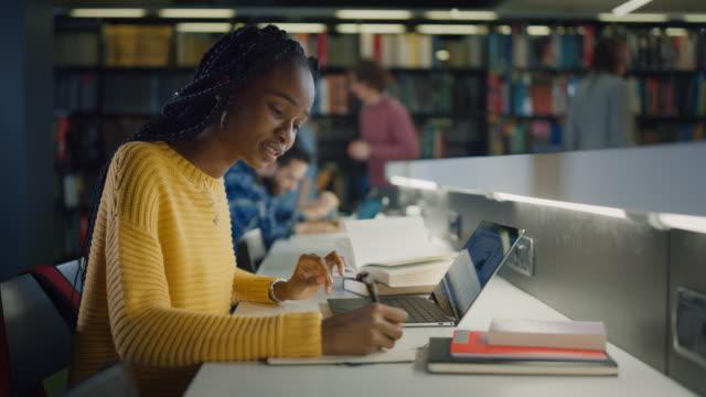 biblioteca universitaria: bella ragazza nera regalata seduta alla scrivania, usa laptop, scrive note per il giornale, saggio, studio per l'assegnazione della classe. gruppo diversificato di studenti che imparano, studiano per gli esami. - esame università video stock e b–roll