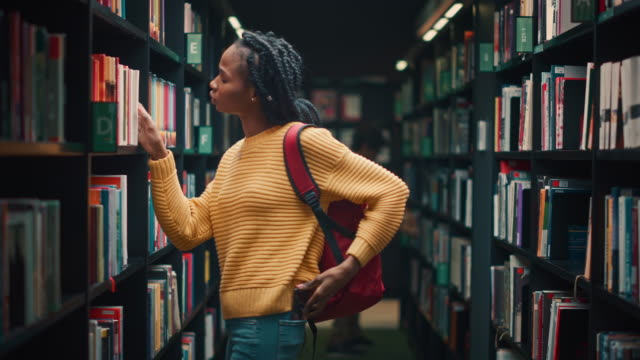 University Library: Portrait of Gifted Beautiful Black Girl Walking Between Rows of Bookshelves Using Smartphone Searching for the Right Book Title, Finds and Picks one for Class Assignment