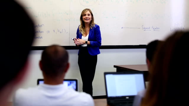 University professor presents classroom lecture University professor lectures to students using classroom whiteboard to discuss advanced education project university student stock videos & royalty-free footage