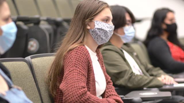 studenti universitari che indossano maschere in classe - studente universitario video stock e b–roll