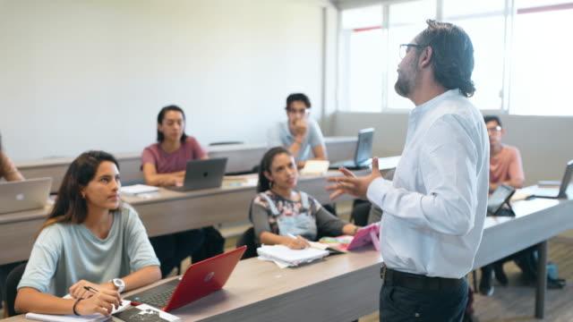 vidéos et rushes de professeur d'université et étudiants dans la salle de classe - 20 24 ans