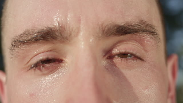 MACRO, DOF: Unknown adult male's eyes after a tough workout in the sunny nature.