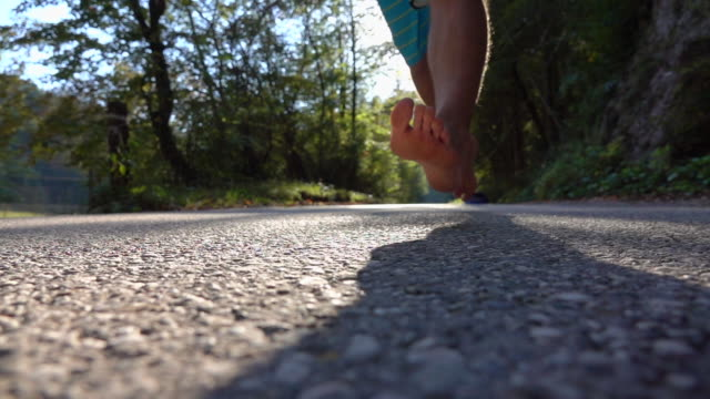 SLOW MOTION, LENS FLARE Unknown barefoot man running alone through autumn forest - video