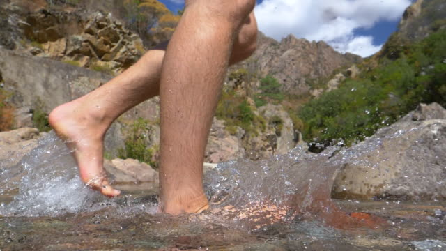 slow motion: unknown barefoot man runs across the crystal clear mountains stream - scalzo video stock e b–roll