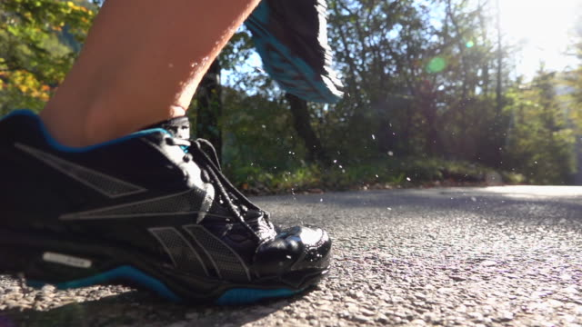 SLOW MOTION CLOSE UP: Unknown girl in trekking shoes running with senior dog. - video