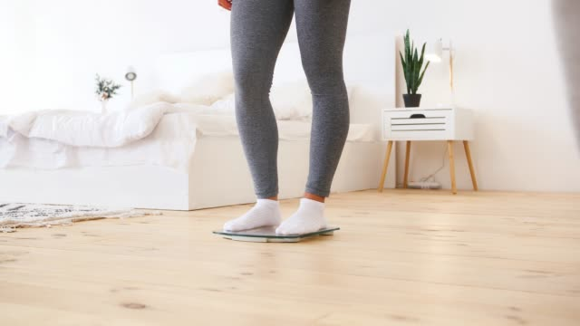 Unknown lady in gray leggings is getting on scales in hope that she has lost weight. Modern home interior. Dieting, health, eating disorder. Close up, pan