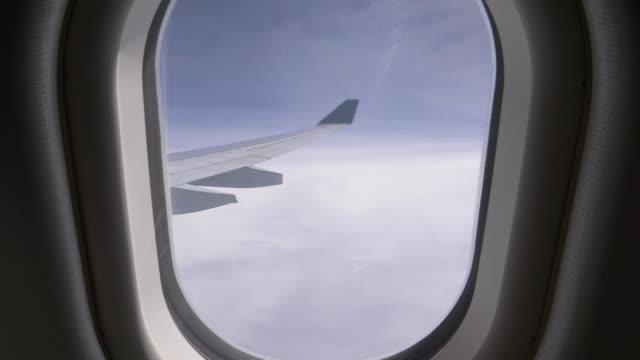 vídeos de stock, filmes e b-roll de pov: pessoa desconhecida puxa avião persiana e revela o céu azul brilhante. - janela