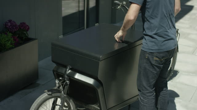 Unloading a toolbox out of  a courier bicycle video