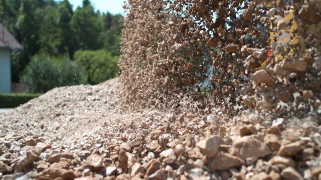 slo mo unloading gravel at the sunny construction site - ghiaia video stock e b–roll