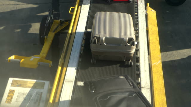 Unloading luggages from the plane at the airport In 4K Slow motion 60fps video