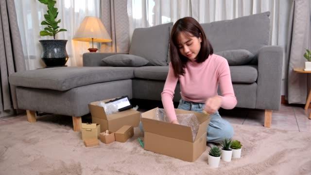 paket und offenes paket beim online-shopping und guter zustellung auspacken. asiatische frau lebensstil im wohnzimmer zu hause. soziale entsung und neue normalität. - weibliche angestellte stock-videos und b-roll-filmmaterial